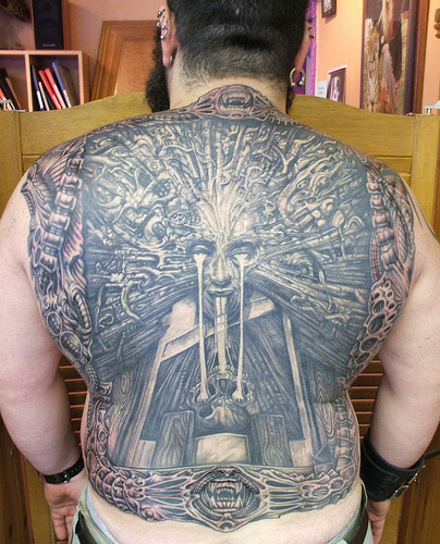 Man's back covered in tattoo
